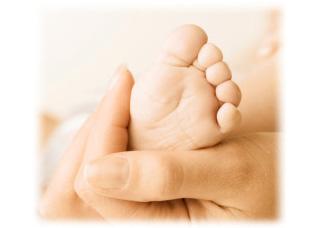 母親の手に包まれた赤ちゃんの足